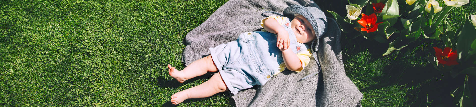 happy baby lying on a blanket placed on well-maintained grass in the garden