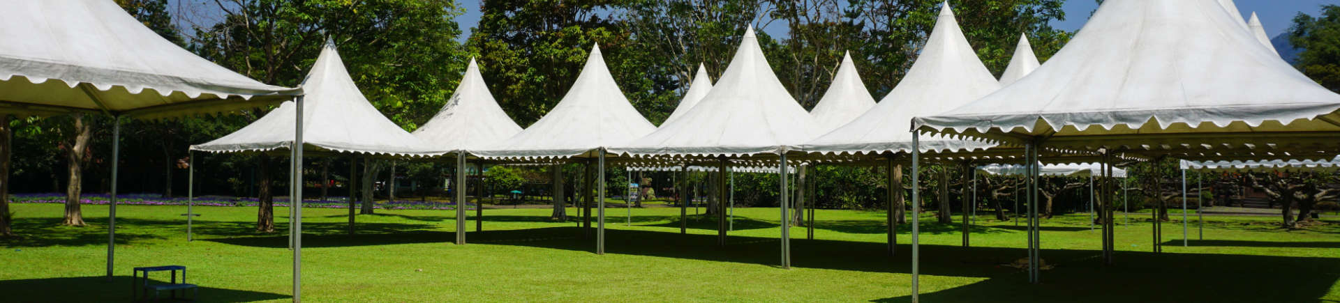 white tents on manicured lawn in garden
